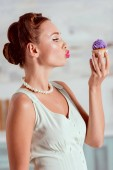 Photo Beautiful pin up girl looking at homemade cupcake and making duck face