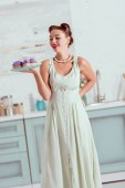 Stylish pin up girl in long dress holding plate full of homemade cupcakes