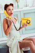 překvapený pin se dívka sedí na osmanské a mluví o vinobraní žluté telefonu