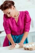 Fotografie elegant pin up girl in crimson dress and blue apron kneeding dough
