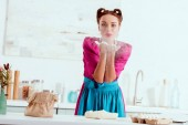 Fotografie cheerful pin up girl blowing off flour from hands