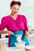 Smiling woman sifting flour on light blue kitchen