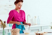 Photo Beautiful pin up girl mixing ingredients for dough