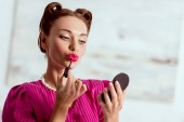 Fotografie Nádherná sponka se dívka dívá na pudr zrcadlo a použití balzám na rty