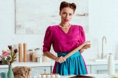 Fotografie Serious pin up girl holding wooden rolling pin while standing by kitchen table