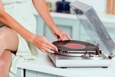 cropped view of pin up girl sitting on table with crossed legs and putting vinyl record on record player