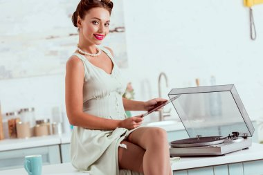 Smiling pin up girl sitting on desk with crossed legs and holding vinyl record