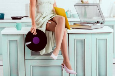 cropped view of pin up girl sitting on table and holding vinyl music record