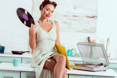 Smiling pin up girl sitting on table with crossed legs and holding vinyl record