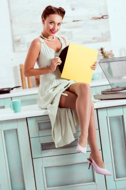 Smiling pin up girl sitting on table and getting vinyl record out of cover