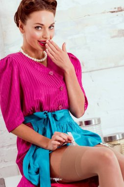 Flirty pin up girl sitting on kitchen table and holding hand near lips