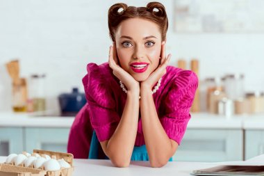 Pretty pin up girl leaning up on kitchen table and looking at camera