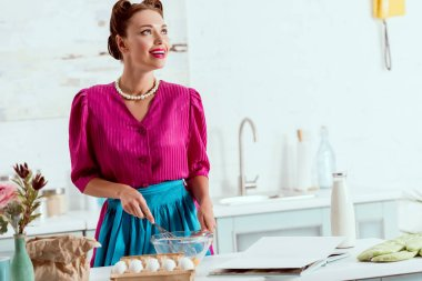 Smiling pin up girl in crimson dress and blue apron mixing ingredients for making dough
