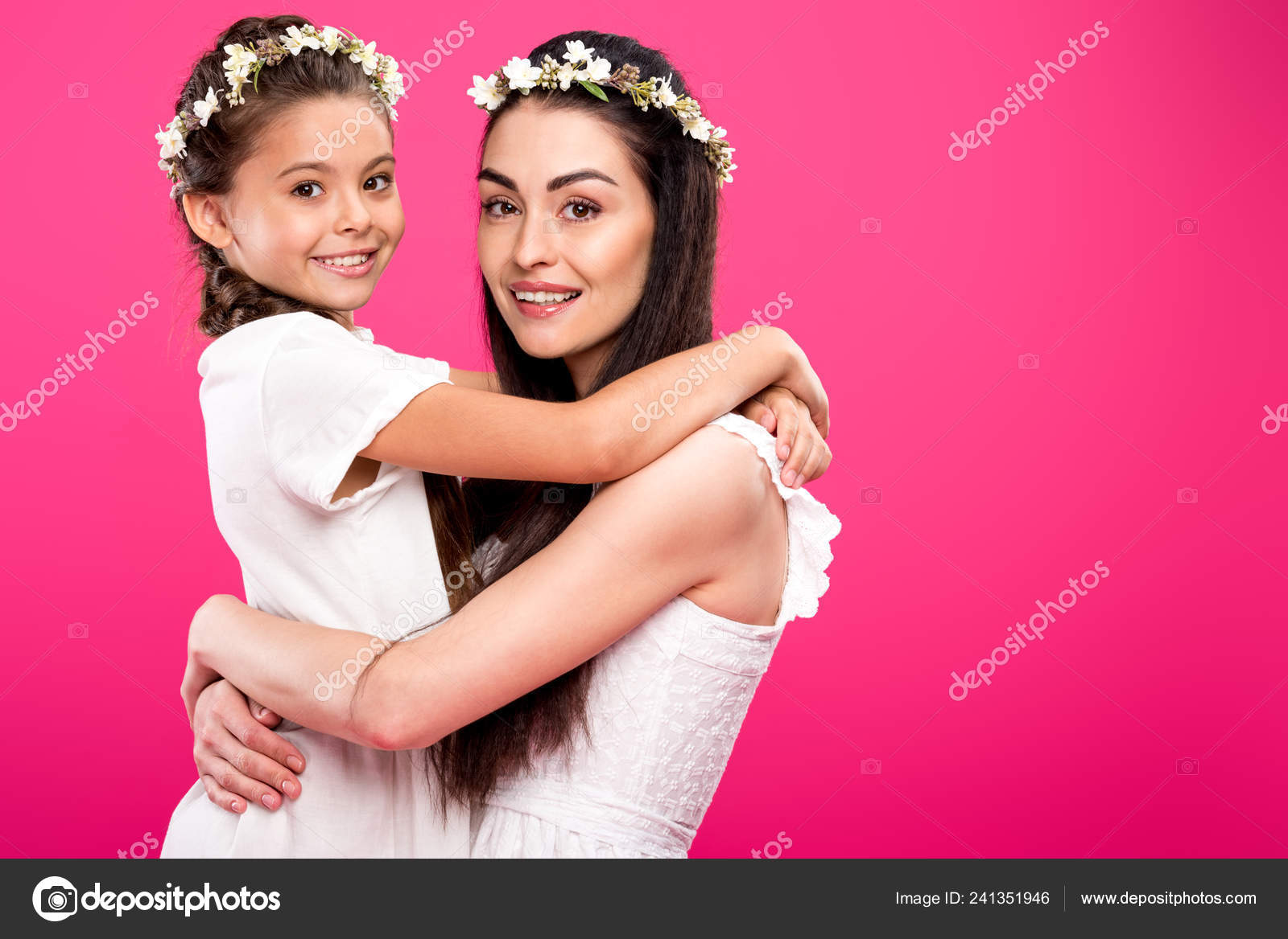 71673b977f Side view of beautiful happy mother and daughter in white dresses and floral  wreaths hugging and smiling at camera isolated on pink — Photo by  AllaSerebrina