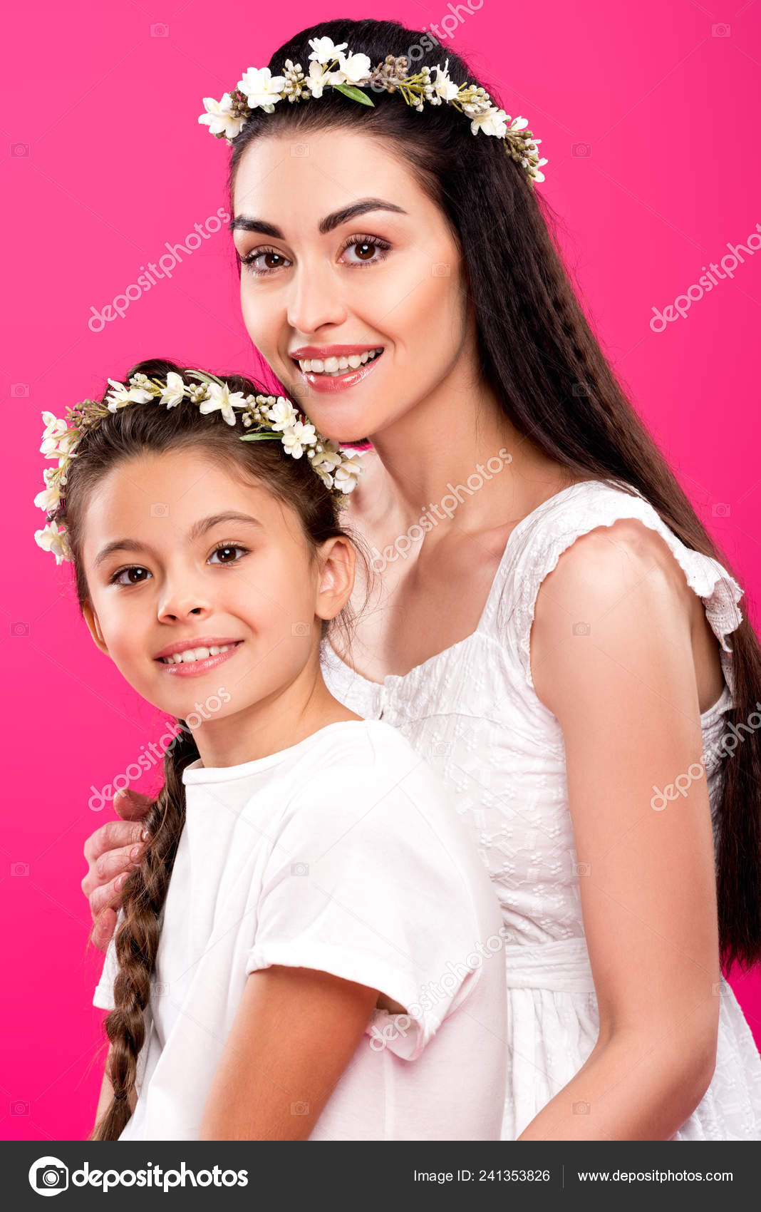 155f96792f Beautiful happy mother and daughter in white dresses and wreaths smiling at camera  isolated on pink– stock image