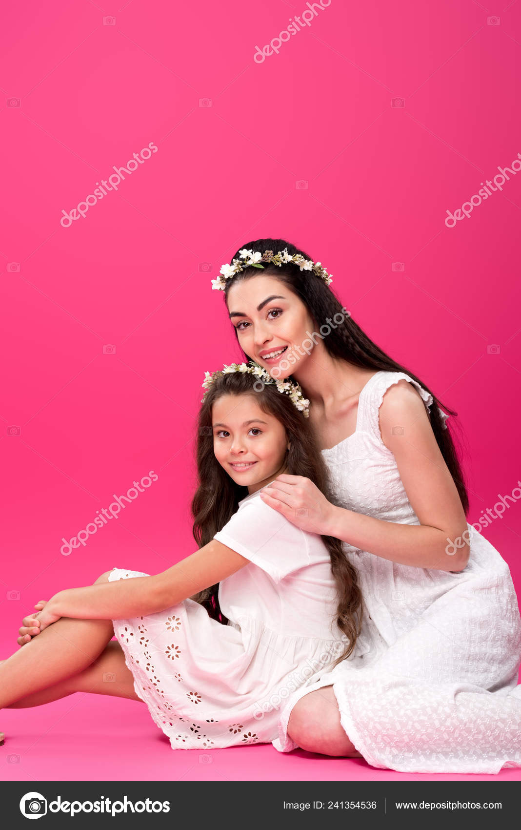 dcdb90c1bb Beautiful happy mother and daughter in white dresses sitting together and  smiling at camera on pink– stock image