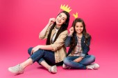 happy mother and daughter holding crowns on party sticks and smiling at camera on pink