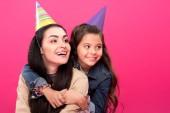 Fényképek boldog anya és lánya átölelve és keres el elszigetelt rózsaszín party kalap