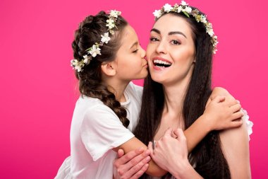 adorable daughter kissing beautiful happy mother isolated on pink