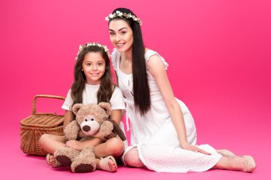 beautiful happy mother and daughter in white dresses sitting with teddy bear and picnic basket on pink