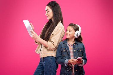 smiling daughter in headphones holding smartphone and looking at mother using digital tablet isolated on pink