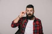 překvapený muž drží brýle, izolované Grey