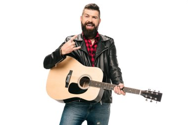 handsome smiling musician in black leather jacket holding acoustic guitar and showing rock and roll sign, isolated on white