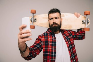 Handsome bearded man in checkered shirt holding longboard and taking selfie on smartphone isolated on grey stock vector