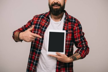 Cropped view of man pointing at digital tablet with blank screen, isolated on grey stock vector