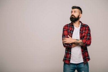 Thoughtful bearded man in checkered shirt isolated on grey with copy space stock vector