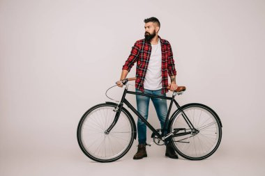 Bearded man in checkered shirt posing with bicycle on grey stock vector