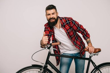 Smiling bearded man posing with bike and showing thumb up isolated on grey stock vector