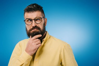 suspicious bearded man in eyeglasses isolated on blue
