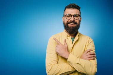 Cheerful bearded man in eyeglasses pointing isolated on blue stock vector