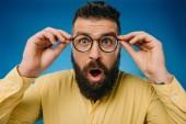 překvapený vousatý muž v brýlích, samostatný na modré