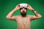 Fotografie Schockierter schöner Mann mit Virtual-Reality-Headset isoliert auf Grün