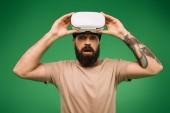 Fotografie Schockierter bärtiger Mann mit Virtual-Reality-Headset isoliert auf Grün