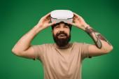 aufgeregt, bärtiger Mann mit virtueller Realität Kopfhörer isoliert auf grün