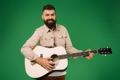 cheerful handsome man playing on acoustic guitar, isolated on green