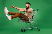 Fotografie excited man gesturing and sitting in shopping cart isolated on green