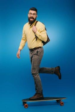 Excited bearded man skateboarding in studio on blue stock vector