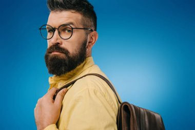 serious bearded man in eyeglasses with backpack, isolated on blue