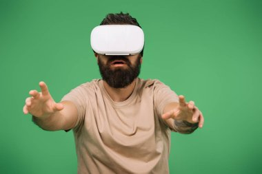 Bearded man gesturing and using Virtual reality headset isolated on green stock vector