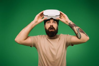 Shocked man with Virtual reality headset isolated on green stock vector
