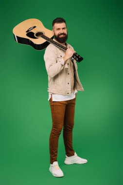 handsome guitarist holding acoustic guitar, isolated on green