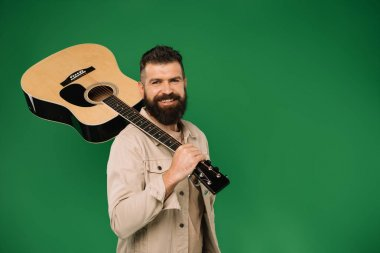 handsome smiling man holding acoustic guitar, isolated on green