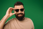 Photo smiling bearded man in sunglasses, isolated on green