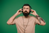 handsome tattooed man listening music in headphones isolated on green