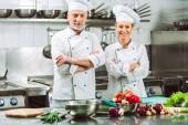 Fotografie ženské a mužské kuchaři v uniformě s rukama zkříženýma během vaření v kuchyni restaurace