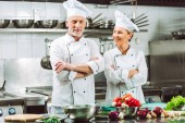 female and male chefs in uniform with arms crossed during cooking in restaurant kitchen